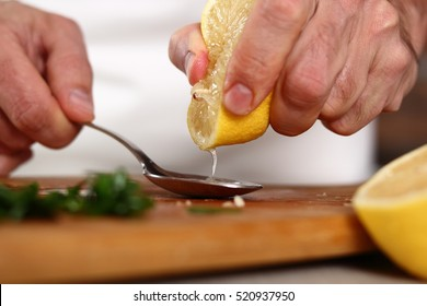 Chef squeezing lemon juice into spoon. Making Chicken and Egg Galette Series.