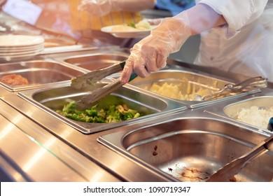 Chefkoch steht hinter einer kompletten Lunch Service Station mit einer Auswahl an Speisen in Schalen.