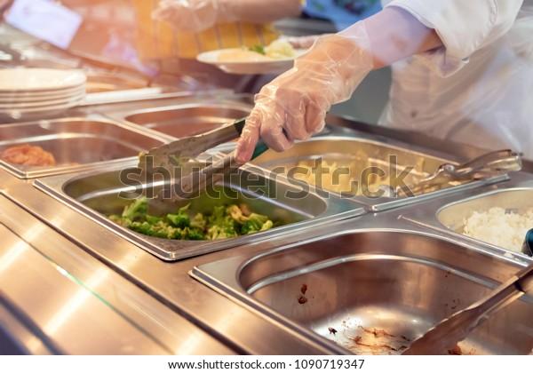 Kocken står bakom full lunch bensinstation med sortiment av mat i brickor.