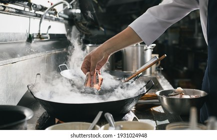 Chef stir fry busy cooking in kitchen. Chef stir fry the food in a frying pan, smoke and splatter the sauce in the kitchen.
