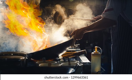 Chef stir fry in wok. Dramatic cooking with fire hard