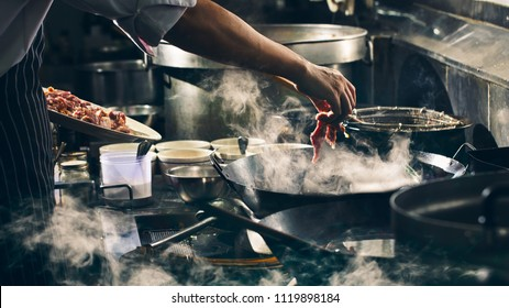 Chef is stirring beef in wok