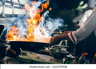 Chef stirring cooking with wok