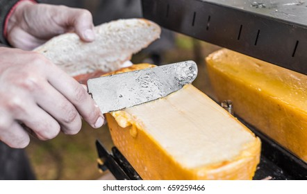 Chef at a street market preparing sandwich with smoked salmon and raclette grilled melted cheese
