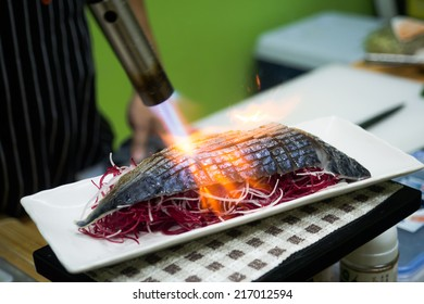 Chef sushi using a torch.