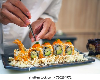 Chef topped ebiko roe over Crispy Salmon crunchy roll, with shrimp tempura, salmon avocado served with wasabi and pickled ginger. Traditional Japanese rice sushi, healthy concept with selective focus.