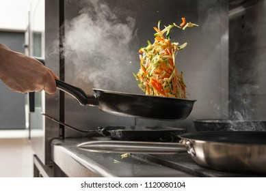 Chef tossing vegetables on frying pan at professional kitchen.