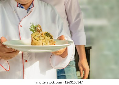 Chef in uniform carrying a plate with wrap with spinach, mushroom and melted cheese and cracker