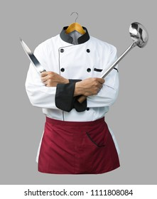 Chef uniform with hand hold knife and ladle on wooden clothes hanger isolated on grey background with clipping path