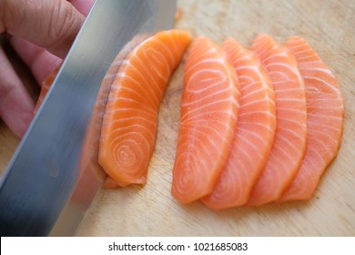 Chef use knife to cutting fresh salmon fillet on chopping board to make salmon slices. Atlantic, Chinook, Chum, Coho, Masu, Pink, Sockeye, Australian, Danube, Hawaiian, and Indian salmon.