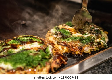 chef use spatula to cut the done okonomiyaki in half on the iron plate, and ready to give the delicious japanese traditional food to the customers