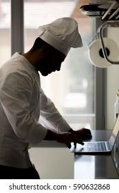 Chef using laptop on worktop