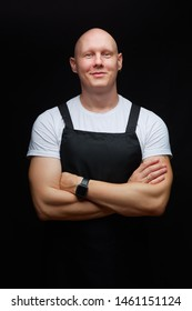 Chef or waiter concept. Strong smiling bald guy wearing black apron on black background.