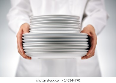 Chef or waitress holding plates in a restaurant kitchen