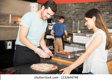 Chef wearing gloves preparing pizza adding pepperoni while customer looking at pizza  in pizzeria