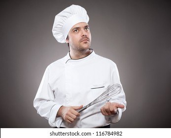 Chef with whisk looking up against grey background