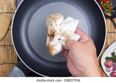 chef wiping the pan before cooking / cooking spicy spaghetti concept
