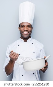 Chef at work. Cheerful young African chef in white uniform mixing something in casserole while standing against grey background