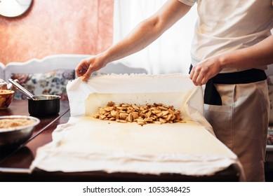 Chef wraps the filling into dough, apple strudel