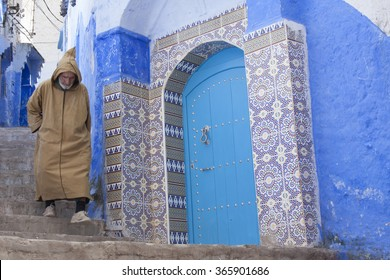 Chefcaouen,Morocco-7th April: man with typical berber dress walks near a blue door in the Medina of Chefcaouen,Morocco,Africa on 7th April 2011