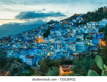 Chefchaouen blue city evening view from the hill with blue houses and street lamps light in Morocco with soft focus