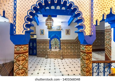 CHEFCHAOUEN, MOROCCO - 12.03.2019: Inner courtyard with tiled walls and floor from mosaic. Traditional ornate and colorful arabesque wall carvings above an archway in Moroccan riad . Inside interior