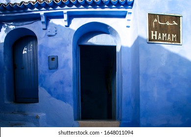 Chefchaouen, Morocco - August 11, 2010: A bright blue wall with a sign saying Hamam in English and Arabic. A hamam is a Turkish Bath, a Middle Eastern variant of a steam bath or a public bathhouse.