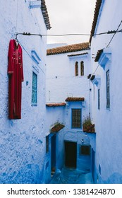 CHEFCHAOUEN, MOROCCO - CIRCA MAY 2018: A red traditional dress hung on a wall in an alley of Chefchaouen, northwest Morocco. The town is famous for its buildings in shades of blue.
