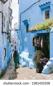CHEFCHAOUEN, MOROCCO - CIRCA MAY 2018: People walking in a small alley in the medina of Chefchaouen, northwest Morocco. The town is famous for its buildings in shades of blue.
