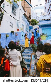 CHEFCHAOUEN, MOROCCO - CIRCA MAY 2018: Tourists lining up to take photo in an alley in the medina of Chefchaouen, northwest Morocco. The town is famous for its buildings in shades of blue.