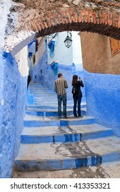 CHEFCHAOUEN, MOROCCO - JANUARY 2, 2014: Tourists walking in beautiful blue medina of Chefchaouen city in Morocco, North Africa