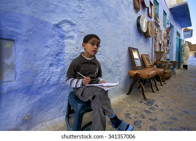 CHEFCHAOUEN, MOROCCO, NOVEMBER 12: Cute young Moroccan Kid studying in the street of the Blue city of Chefchaouen, one of the trendiest destination. Morocco 2010.