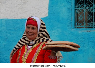 Chefchaouen, Morocco - October 30, 2016: Woman dressed in typical moroccan attire selling bread on a street in Chefchaouen, Morocco