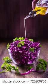 Chef's hand pouring oil on red cabbage salad.