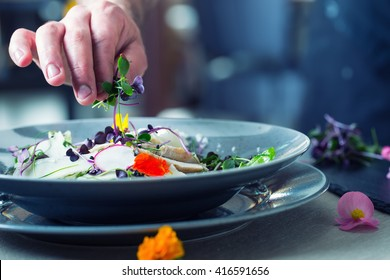 Chefs hand prepares a salad with chicken meat and decorates this meal with herbs and edible flowers.