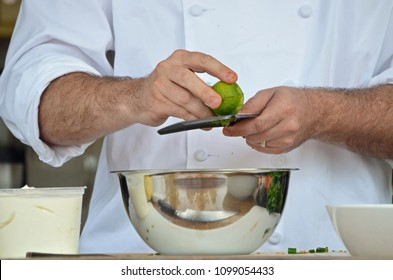 chef's hands zesting a lime, reflection in the bowl of cutting board and food at a chef demonstration