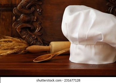 Chef's hat in rustic setting with vintage wooden spoon and rolling pin on wood cutting board..  Decorative, carved serving tray as background.  Baking or Cooking concept.