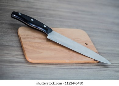Chef's knife and Chopping board on wood table.