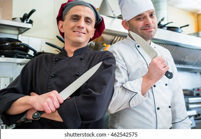 Chefs posing with knife in their restaurant kitchen