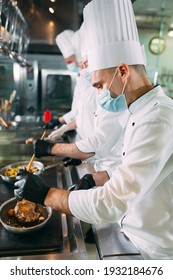 Chefs in protective masks and gloves prepare food in the kitchen of a restaurant or hotel