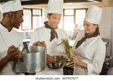 Chefs talking while preparing food in commercial kitchen