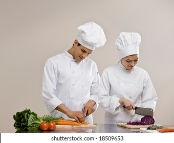 Chefs in toques and chef?s whites preparing and chopping fresh vegetables together