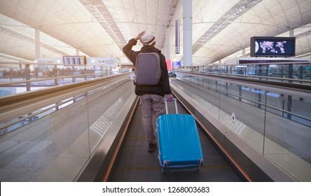 Chek Lap Kok-Hong Kong International Airport-Hong kong-December-7-2018:Young man  with backpack and suitcase in the airport departure lounge , traveler suitcases in airport terminal.