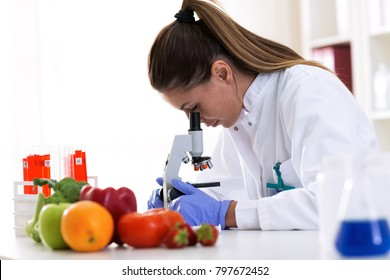 Cheking food quality at professional lab with microscope, advanced food technology