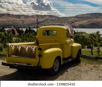 Chelan, Chelan / USA - 09 13 2018: Bright yellow Ford truck with hay in back parked in dirt parking lot by Lake Chelan with beautiful countryside behind it