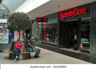 CHELMSFORD - ENGLAND 1ST SEPTEMBER 2015 - Shoppers sit and rest on public seating in a  Chelmsford shopping center during the summer of 2015 in England