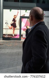 CHELMSFORD, ENGLAND 7TH NOVEMBER 2017 - Man looks at a rollerskater woman advertisement as he walks along Bond Street in Chelmsford in the daytime