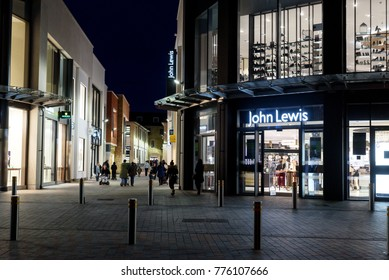 CHELMSFORD, ENGLAND 7TH NOVEMBER 2017 - Shoppers at night outside the English high street shop with lit sign