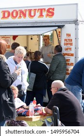 CHELMSFORD, ESSEX/ENGLAND - 1ST JUNE 2019 - People visiting a car boot sale in Boreham Essex buying fast food bugers and donuts and where they can also buy cheap and unusual items during the summer
