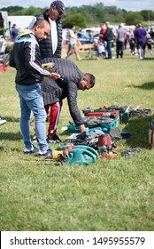 CHELMSFORD, ESSEX/ENGLAND - JUNE 1ST 2019 - Men visiting a car boot sale in Boreham Essex where they are looking at drills and tools for work and can also buy cheap and unusual items during the summer